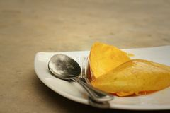 Yellow peel mango with fork on white plate. Stock Images