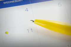 Yellow pen points to the number 4 on calendar background. Stock Photography