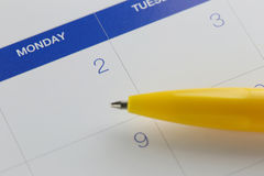 Yellow pen points to the number 2 on calendar background. Stock Images