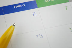 Yellow pen points to the number 6 on calendar background. Royalty Free Stock Image