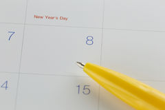 Yellow pen points to the number 8 on calendar background. Stock Images
