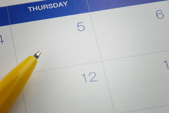 Yellow pen points to the number 5 on calendar background. Royalty Free Stock Images
