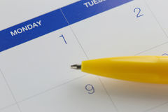 Yellow pen points to the number 1 on calendar background. Royalty Free Stock Images