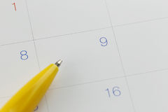 Yellow pen points to the number 9 on calendar background. Stock Photo