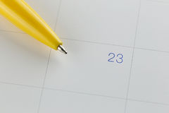 Yellow pen points to the number 23 on calendar background. Yellow pen points to the number 23 on calendar background in concept of appointment schedules and Royalty Free Stock Photo
