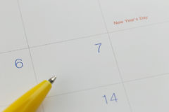 Yellow pen points to the number 7 on calendar background. Royalty Free Stock Photo
