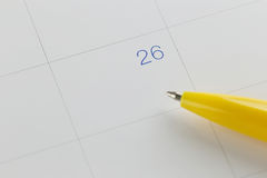yellow pen points to the number 26 on calendar background. Stock Images