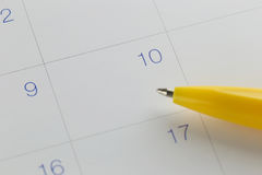 yellow pen points to the number 10 on calendar background. Royalty Free Stock Images