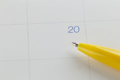 yellow pen points to the number 20 on calendar background. Royalty Free Stock Images