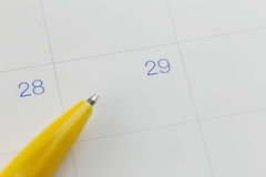 Yellow pen points to the number 29 on calendar background. Yellow pen points to the number 29 on calendar background in concept of appointment schedules and Royalty Free Stock Images