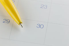 Yellow pen points to the number 30 on calendar background. Yellow pen points to the number 30 on calendar background in concept of appointment schedules and Royalty Free Stock Images