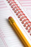 Yellow pencil on agenda. A closeup view of a yellow pencil with an eraser, on a day planner/agenda stock photo