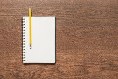 Yellow pencil with blank note book on wooden background Royalty Free Stock Photos
