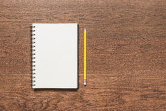 Yellow pencil with blank note book on wooden background Royalty Free Stock Photography