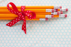 Yellow pencil bouquet. A cluster of yellow pencils is tied up in a red polka dot bow on an blue and white polka dot background Stock Image
