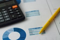 Yellow pencil, calculator and blue pie chart. Horizontal photo of yellow pen placed on paper sheets with blue pie charts with black calculator in background Stock Image