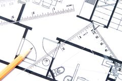Yellow pencil and a floor plan. A yellow pencil and a geometric tools on top of floor plan stock photo
