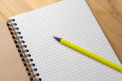 Yellow pencil on a notebook with sheets in a cage on a wooden table. Concept for shopping list, notes, planning. Top royalty free stock image