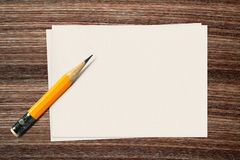 Yellow pencil and paper on wood background Royalty Free Stock Photos