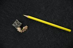 Yellow pencil sharpener and sharpened rubbish. On a dark textured background royalty free stock images