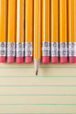 Yellow Pencils & Erasers on Paper. Closeup Macro of Yellow Tablet with lines and yellow pencil erasers and single sharpened lead pencil Royalty Free Stock Photo