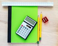 2 pencils, a pencil sharpener, a calculator, a triangular ruler, and a green notebook on a wooden desk royalty free stock image