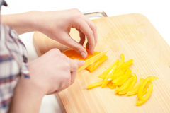 Yellow pepper being cut on slicing board Royalty Free Stock Images