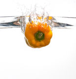 Yellow pepper falling in water Royalty Free Stock Image