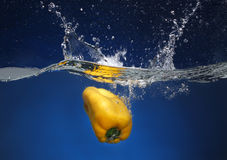 Yellow pepper falling into water Stock Photos