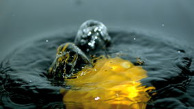 Yellow pepper falling in water close up stock footage