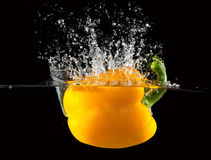 Yellow pepper falls in the water Royalty Free Stock Images
