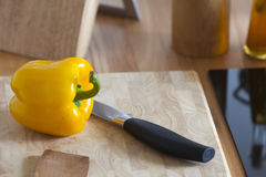 Yellow Pepper lies with a Kitchen Knife on a Cutting Board Stock Photos