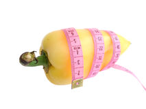 Yellow pepper with pink tape measure against white background stock images