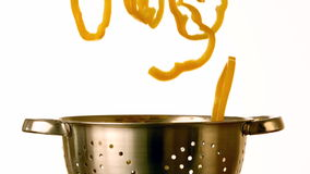 Yellow pepper slices falling into colander stock video