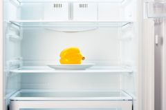 Yellow pepper on white plate in open empty refrigerator Royalty Free Stock Photography