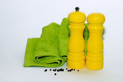 Yellow pepper and yellow salt shaker. And green towel on a white background royalty free stock photography