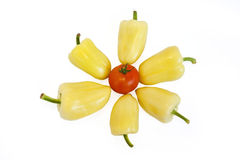 Yellow peppers lying on white background. In the middle is a red tomato Royalty Free Stock Photo