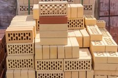Yellow perforated bricks on pallet on an outdoor warehouse. Yellow perforated bricks with rectangular holes on pallet among of other bricks on an outdoor Royalty Free Stock Image