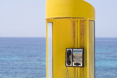 Yellow phone, blue sea Royalty Free Stock Image