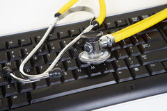 Yellow phonendoscope and black keyboard Stock Images