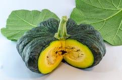 Yellow piece pumpkin and green pumpkin  leaf on white backg Stock Photo