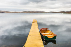 Yellow pier and yellow boat on the lake. Stock Photo
