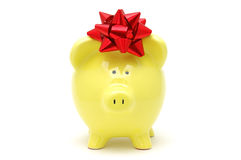 Yellow piggy bank with bow Stock Photo