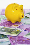 Yellow piggy bank on euro banknotes. Yellow piggy bank surrounded by euro banknotes Stock Photo