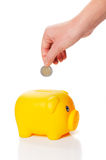 Yellow piggy bank is getting two euro coin from a hand Royalty Free Stock Images