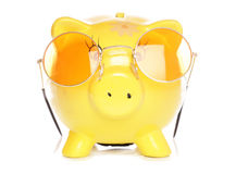 Yellow piggybank with sunglasses Royalty Free Stock Images
