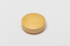 A yellow pill on white background. An isolated yellow round pill on white background Stock Image