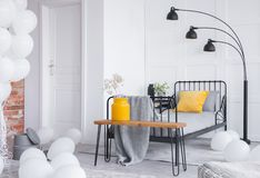 Grey bed and yellow vase with white flowers on wooden bench in stylish industrial bedroom. Yellow pillow on the grey bed and yellow vase with white flowers on stock photography