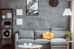 Yellow pillow on grey settee Royalty Free Stock Photography