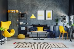 Yellow pillow on grey sofa. Blue blanket in contemporary living room with yellow pillow on grey sofa stock images